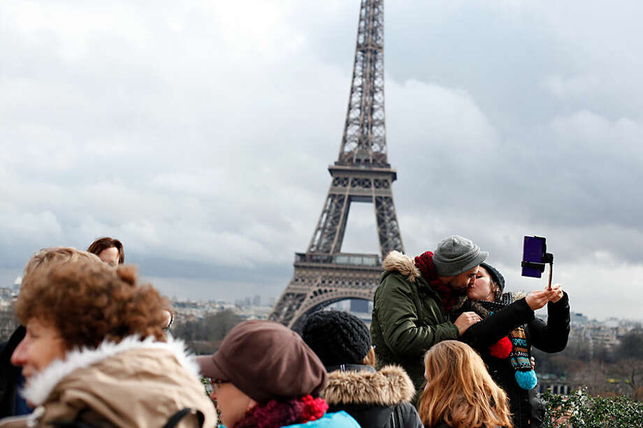 A couple kiss in front of the Eiffel Tower, during Valentine's day in Paris, Saturday, Feb. 14, 2015. Valentine's Day is observed on February 14 each year as a special day to celebrate love and romance. (AP Photo/Thibault Camus)