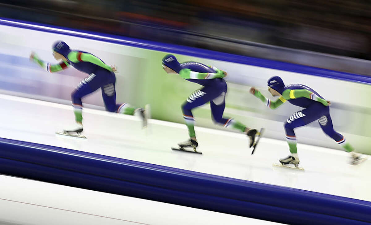 Team Netherlands with Sven Kramer, center, Koen Verweij, left, and Douwe de Vries, right, compete to take a gold medal during the men's team pursuit race of the speedskating single distance world championships at Thialf ice rink in Heerenveen, Netherlands, Friday, Feb. 13, 2015. (AP Photo/Peter Dejong)