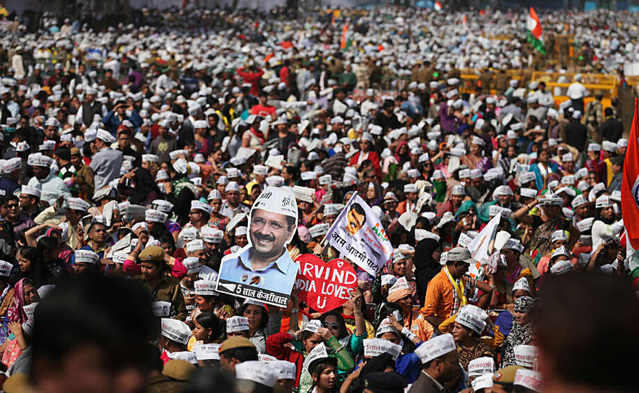 Supporters of Aam Aadmi Party, or Common Man's Party, gather to witness the swearing-in ceremony of party leader Arvind Kejriwal as chief minister of Delhi in New Delhi, India, Saturday, Feb. 14, 2015. The AAP, headed by the former tax official who had remade himself into a champion for clean government, won 67 of the 70 seats in recent elections. Kejriwal and the party he created routed the country's best-funded and best-organized political machine and dealt an embarrassing blow to Prime Minister Narendra Modi. (AP Photo/Altaf Qadri)