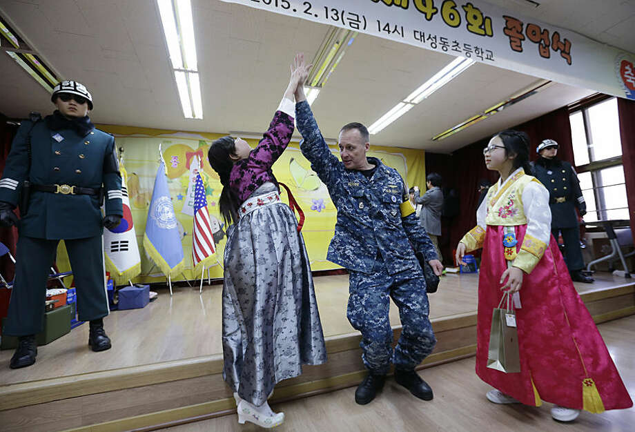 """Graduate Park Jin, left, is congratulated by U.S. Navy LCDR Daniel E. """"Dan-o"""" McShane of Charlotte, NC. after a graduation ceremony as South Korean border guard soldiers stand on the stage at the Tae Sung Dong Elementary School in Paju, South Korea, near Panmunjom inside the Demilitarized Zone separating South and North Korea, Friday, Feb. 13, 2015. The school is located just a few hundred meters from the fenced and mined border with North Korea. Four students graduated from the school Thursday. (AP Photo/Ahn Young-joon, Pool)"""