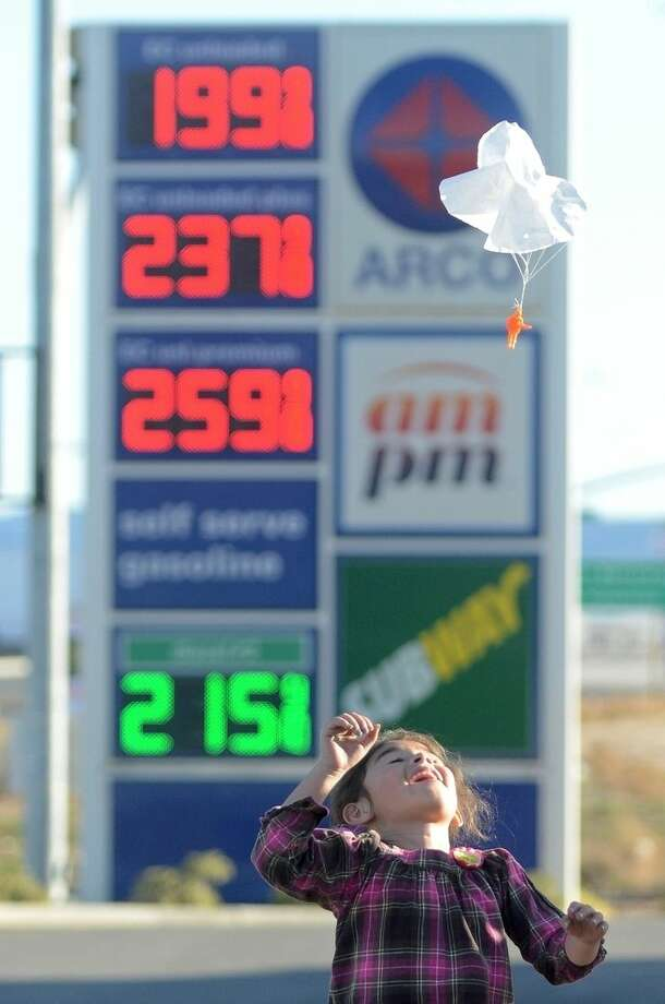 FILE - In this Wednesday, Feb. 24, 2016, file photo, Joanna Alvarez plays with a toy parachute man at an Arco gas station parking lot in Oak Hills, Calif. Gasoline prices are expected to keep rising until summer but remain far cheaper than recent years, due to the worldwide glut of oil. (David Pardo/Victor Valley Daily Press via AP, File)