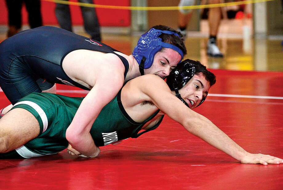 Hour photo / Erik Trautmann Local wrestlers Camilo Builes of Norwalk and Dominic Leckie of Stamford compete in the FCIACChampionship meet at New Canaan High School Saturday.