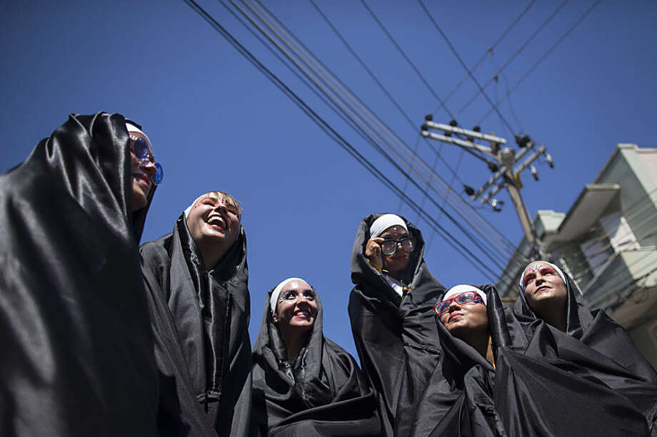 """Revelers dressed as nuns perform during the """"Carmelitas"""" carnival parade in Rio de Janeiro, Brazil, Friday, Feb. 13, 2015. Carmelitas is a band started in 1990 by a group of friends who gathered for soccer and drinks just outside a Carmelite convent. Jokes about the possibility of nuns escaping to join the party gave rise to the band, which parades twice: once at the beginning of Carnival, when the nuns escape the convent to join the fun, and then on the last day, when they return to their cloistered existence. (AP Photo/Felipe Dana)"""