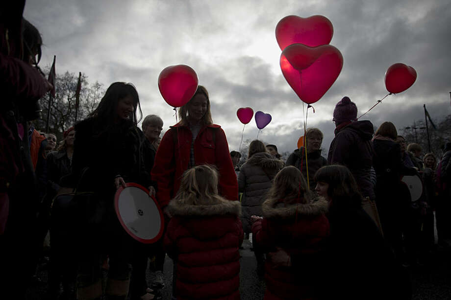 Women and girls hold love heart shaped balloons during a day of action event with a theme of love revolution and a focus on healthy relationships organized by the One Billion Rising movement at Marble Arch in London, on Valentine's Day, Saturday, Feb. 14, 2015. One Billion Rising is so named to give awareness to the statistic that one in three women in the world will be raped or beaten in their lifetime which equates to one billion women. (AP Photo/Matt Dunham)