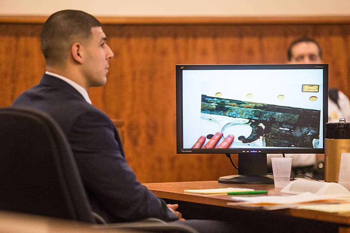 Former New England Patriots football player Aaron Hernandez, left, listens as a photo of a small handgun found in a wooded area near the crime scene was displayed during his murder trial, Friday, Feb. 13, 2015, in Fall River, Mass. Hernandez is charged with killing semiprofessional football player Odin Lloyd. (AP Photo/The Boston Globe, Aram Boghosian, Pool)