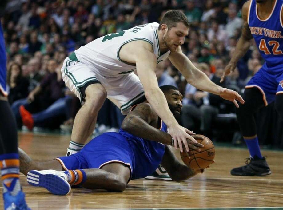 New York Knicks' Kyle O'Quinn, bottom and Boston Celtics' Tyler Zeller battle for a loose ball during the first quarter of an NBA basketball game in Boston, Friday, March 4, 2016. (AP Photo/Michael Dwyer)