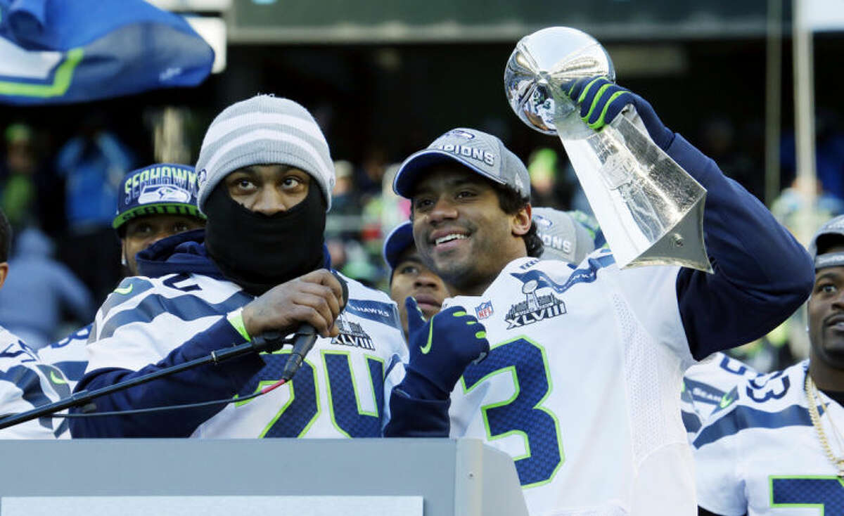 Seattle Seahawks quarterback Russell Wilson, right, lifts the Vince Lombardi Trophy next to Seahawks running back Marshawn Lynch, left, during a rally on Wednesday, Feb. 5, 2014, in Seattle. The Seahawks defeated the Denver Broncos on Sunday in NFL football's Super Bowl XLVIII game in East Rutherford, N.J. (AP Photo/Ted S. Warren)