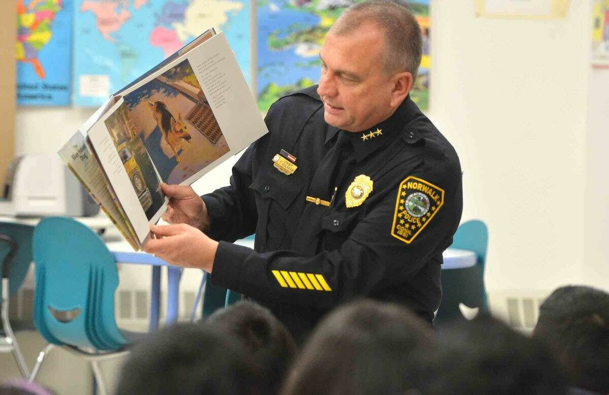 Hour Photo/Alex von Kleydorff Norwalk Police Chief Tom Kulhawik reads The Blue House Dog to kids during Read Across America day at Brookside School