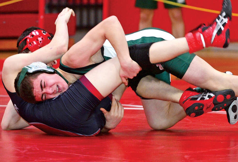 Hour photo / Erik Trautmann Norwalk Mike Malozzi competes against Fairfield Warde opponent in the FCIAC Championship meet at New Canaan High School Saturday.