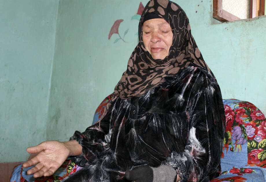 In this Feb. 16, 2016 photo, Um Muhammed speaks about the death of her son, Mohammed Hamdan, at the family house in Beni Suleiman village, south of Cairo, Egypt. The 32-year-old Egyptian government engineer disappeared in mid-January when, according to witnesses, masked police burst into his office in the southern city of Beni Suef and dragged him off in handcuffs in front of his co-workers. (AP Photo/Maggie Michael)