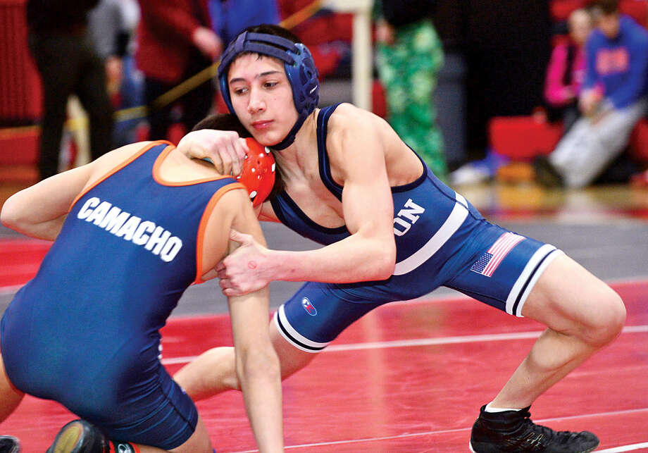 Hour photo / Erik Trautmann Local wrestler Nick Rende of Witon and Jake Camacho of Danbury compete at 106 in the FCIACChampionship meet at New Canaan High School Saturday.