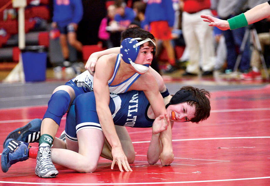 Hour photo / Erik Trautmann Local wrestlers Finn McGovern of Wilton and Zach Taylow of Ludlowe compete at 99 in the FCIAC Championship meet at New Canaan High School Saturday.