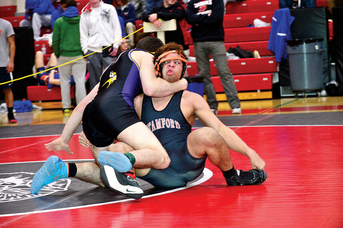 Hour photo / Erik Trautmann Local wrestlers compete in the FCIAC Championship meet at New Canaan High School Saturday.