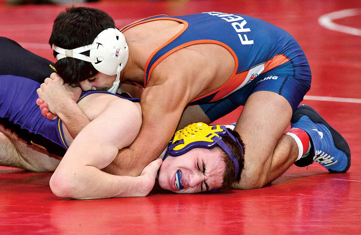 Hour photo / Erik Trautmann Local wrestlers Andrew Blum of Westhill and Palo Freitas of Danbury compete in the FCIAC Championship meet at New Canaan High School Saturday.