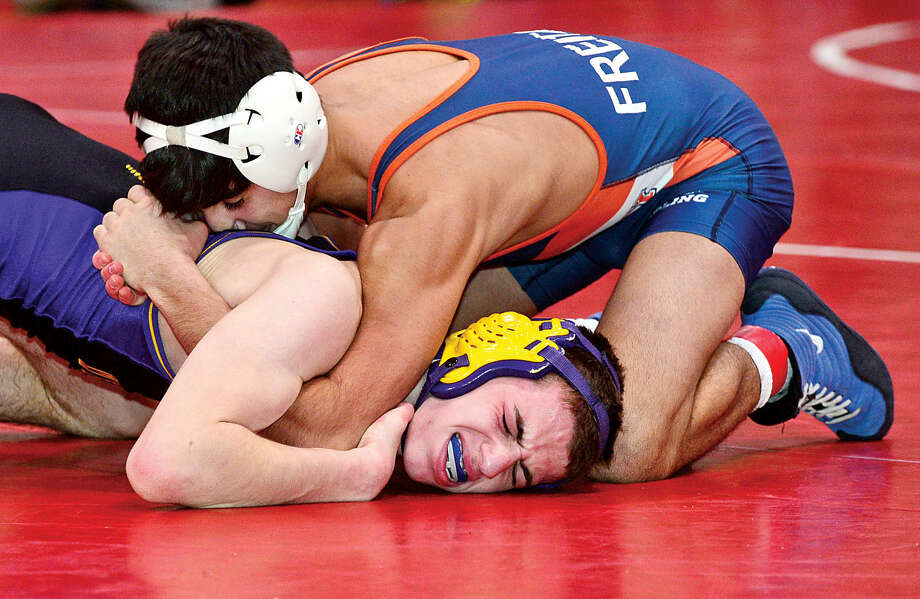Hour photo / Erik Trautmann Local wrestlers Andrew Blum of Westhill and Palo Freitas of Danbury compete in the FCIACChampionship meet at New Canaan High School Saturday.