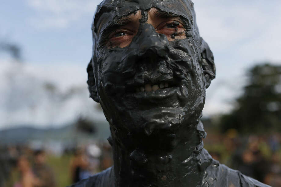 """A mud covered reveler poses for the picture during the traditional """"Bloco da Lama"""" or """"Mud Block"""" carnival party, in Paraty, Brazil, Saturday, Feb. 14, 2015. Legend has it the """"bloco"""" was born in 1986 after local teens hiking in a nearby mangrove forest smeared themselves with mud to discourage mosquitoes and then wandered through Paraty. The party grew year after year, but revelers eventually were banned from parading in the colonial downtown after shopkeepers complained pristine white walls were stained with the hard-to-remove mud. (AP Photo/Leo Correa)"""