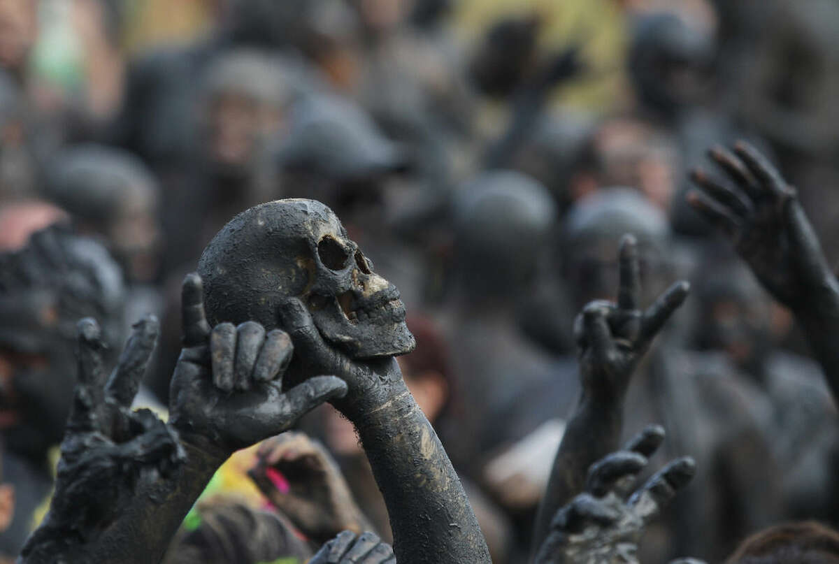 A man holds up a skull during the traditional