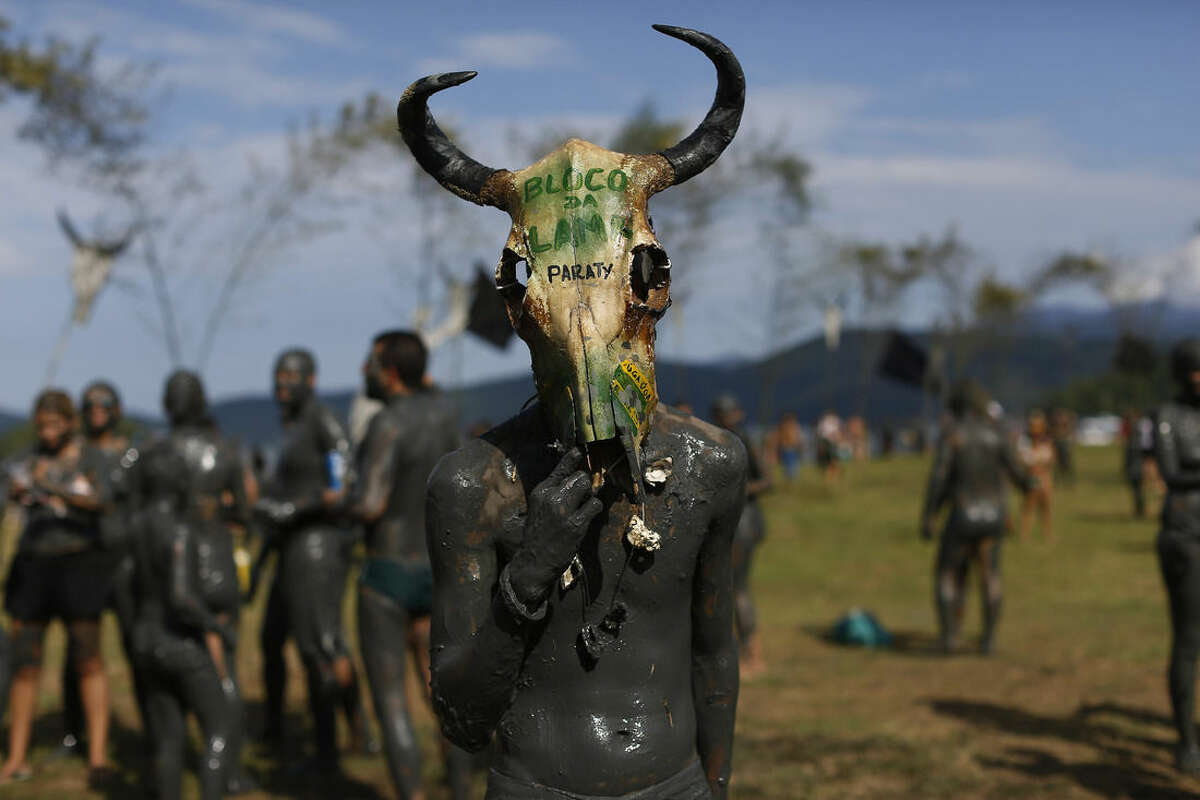 A mud covered reveler wearing a cow's skull as a mask poses for a photo during the traditional