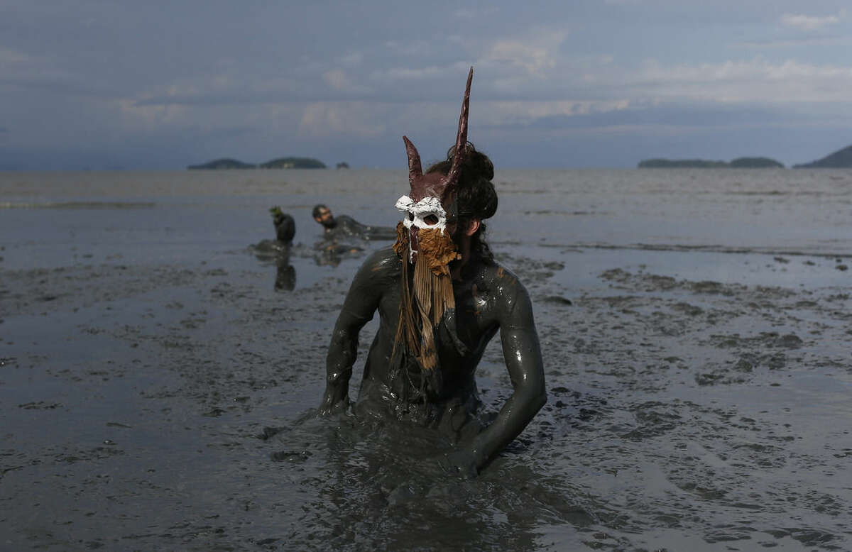A reveler wearing a costume plays in the mud during the traditional
