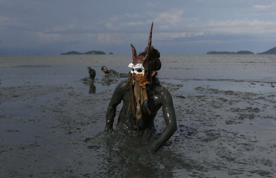"""A reveler wearing a costume plays in the mud during the traditional """"Bloco da Lama"""" or """"Mud Block"""" carnival party, in Paraty, Brazil, Saturday, Feb. 14, 2015. Legend has it the """"bloco"""" was born in 1986 after local teens hiking in a nearby mangrove forest smeared themselves with mud to discourage mosquitoes and then wandered through Paraty. The party grew year after year, but revelers eventually were banned from parading in the colonial downtown after shopkeepers complained pristine white walls were stained with the hard-to-remove mud. (AP Photo/Leo Correa)"""