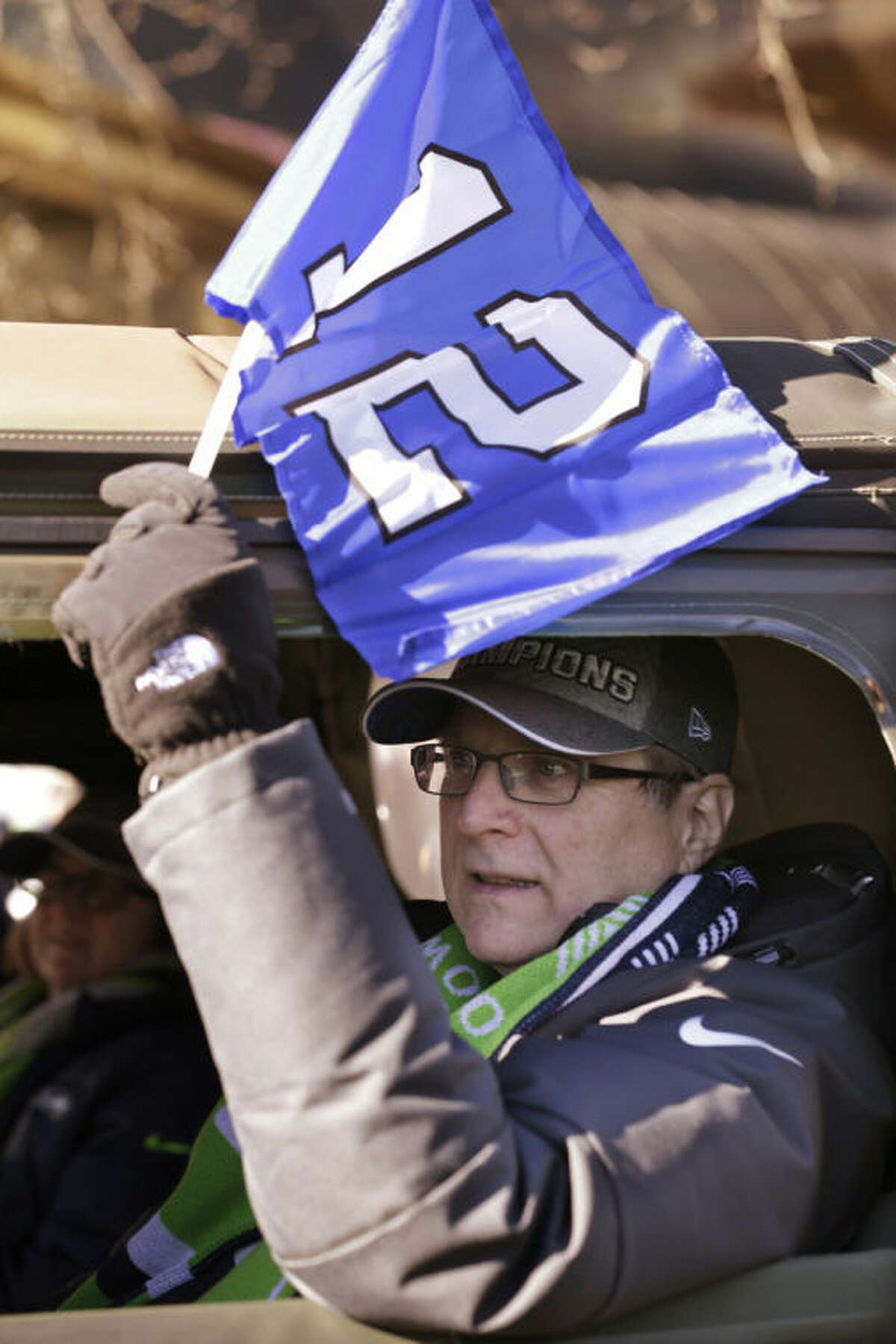 Seattle Seahawks owner Paul Allen waves a 12th Man flag out of his window as he rides in a parade for the NFL football Super Bowl champions Wednesday, Feb. 5, 2014, in Seattle. The Seahawks defeated the Denver Broncos 43-8 on Sunday. (AP Photo/Elaine Thompson)