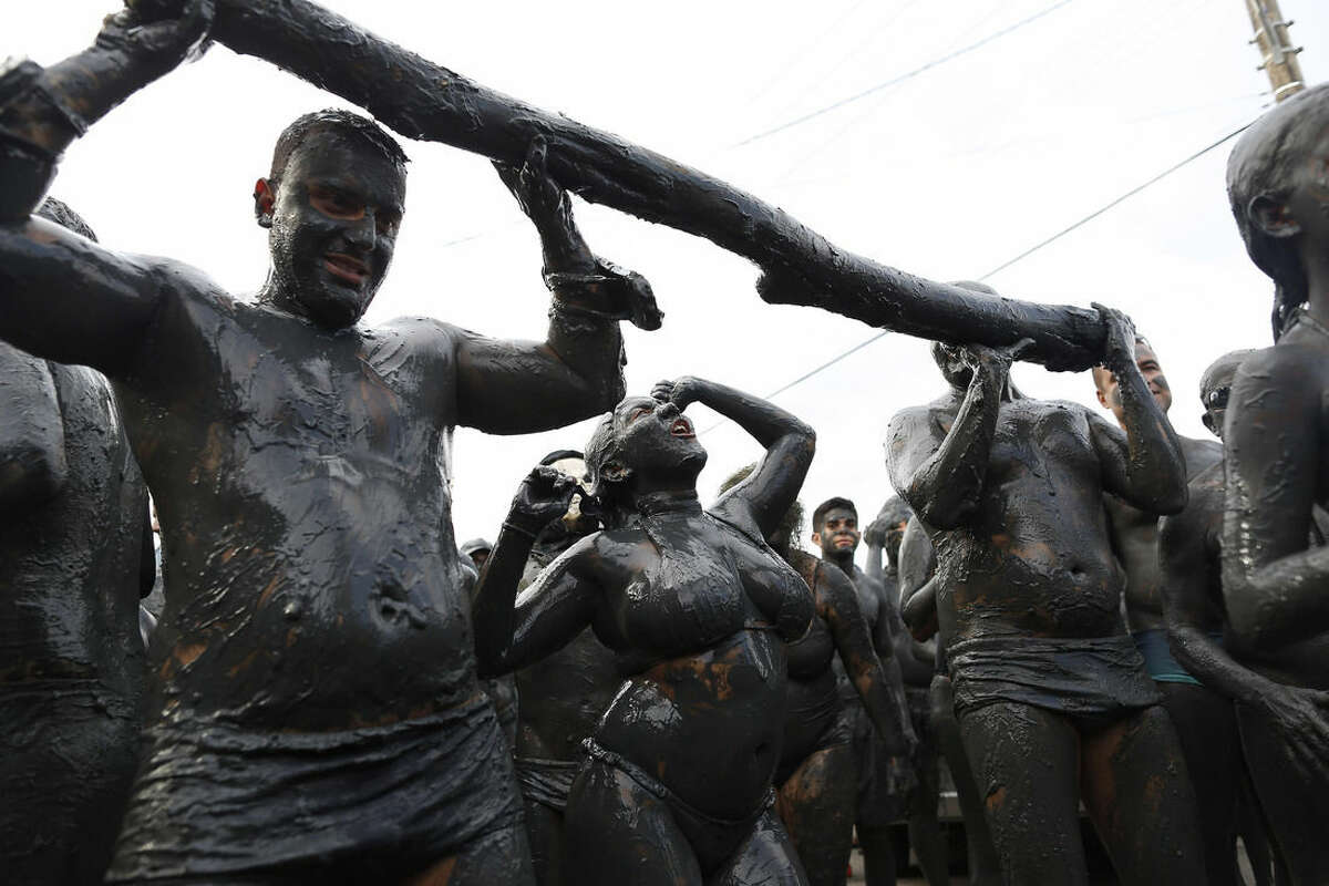People covered in mud dance during the traditional