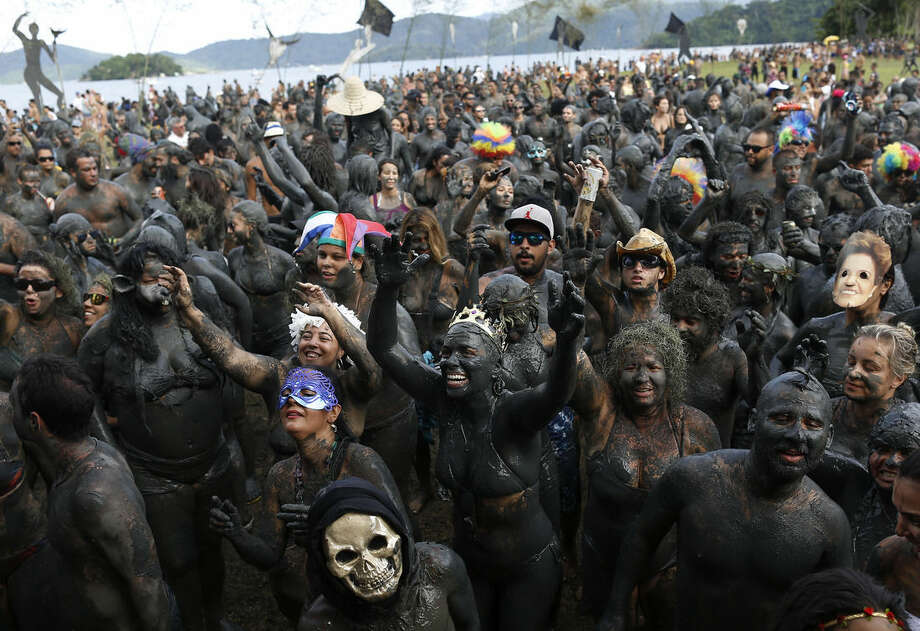 "People covered in mud attend the traditional ""Bloco da Lama"" or ""Mud Block"" carnival party, in Paraty, Brazil, Saturday, Feb. 14, 2015. Legend has it the ""bloco"" was born in 1986 after local teens hiking in a nearby mangrove forest smeared themselves with mud to discourage mosquitoes and then wandered through Paraty. The party grew year after year, but revelers eventually were banned from parading in the colonial downtown after shopkeepers complained pristine white walls were stained with the hard-to-remove mud. (AP Photo/Leo Correa)"