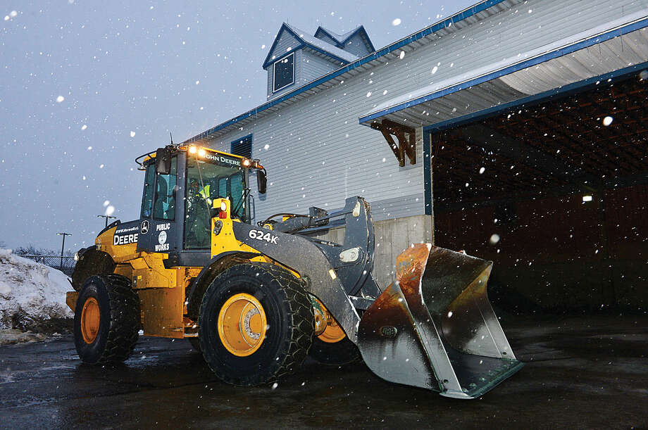 Hour photo / Erik Trautmann DPW employees begin a long shift ahead of the snowstorm Saturday evening.