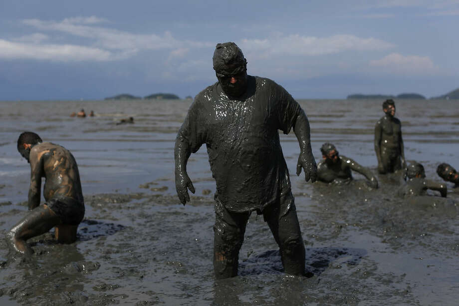 "A mud covered reveler plays in the mud during the traditional ""Bloco da Lama"" or ""Mud Block"" carnival party, in Paraty, Brazil, Saturday, Feb. 14, 2015. Revelers in the seaside colonial town threw themselves into deposits of black, mineral-rich slime, emerging covered head-to-toe in the sludge. Bikinis and trunks disappeared beneath the mud, which highlights both gym-pumped pectorals and beer-fed guts. (AP Photo/Leo Correa)"
