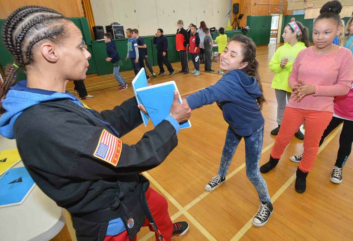 Hour Photo/Alex von Kleydorff Fox Run 5th grader Samantha Poncé is able to chop the panel in half with Sensei Trish Jackson from Kempo Academy during the school's Celebration of the Arts program