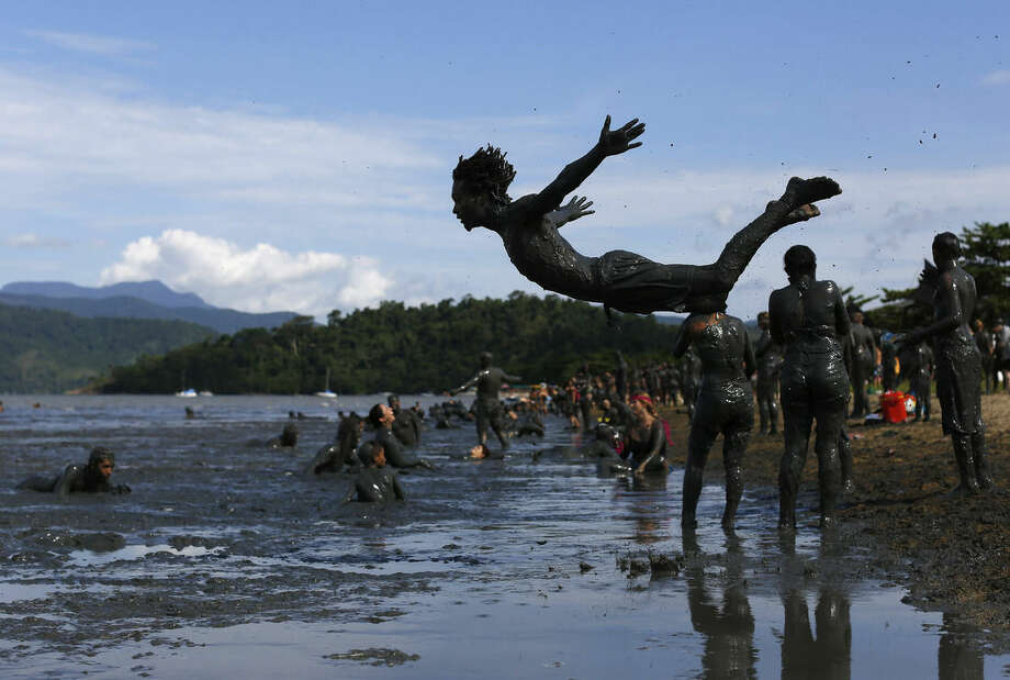 "A man jumps into the mud during the traditional ""Bloco da Lama"" or ""Mud Block"" carnival party, in Paraty, Brazil, Saturday, Feb. 14, 2015. Revelers in the seaside colonial town threw themselves into deposits of black, mineral-rich slime, emerging covered head-to-toe in the sludge. Bikinis and trunks disappeared beneath the mud, which highlights both gym-pumped pectorals and beer-fed guts. (AP Photo/Leo Correa)"