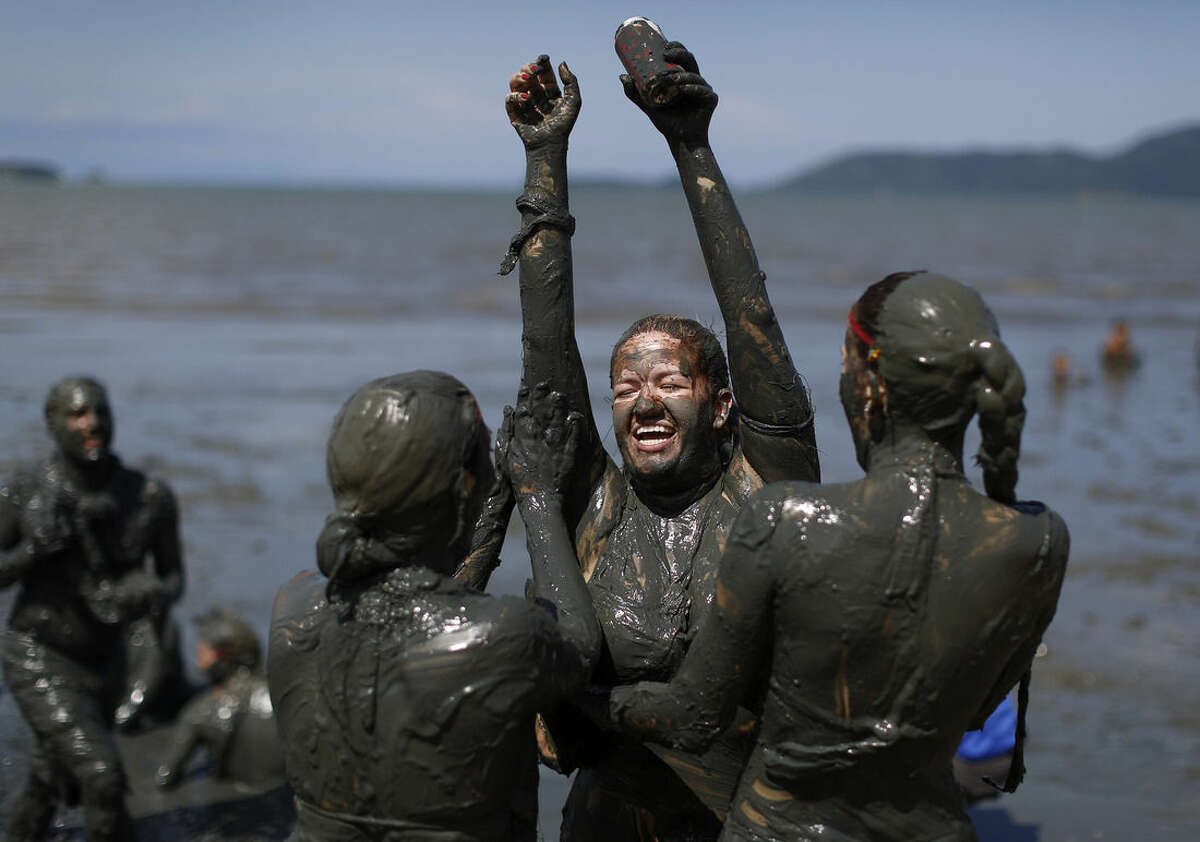 Revelers cover a freind in mud during the traditional