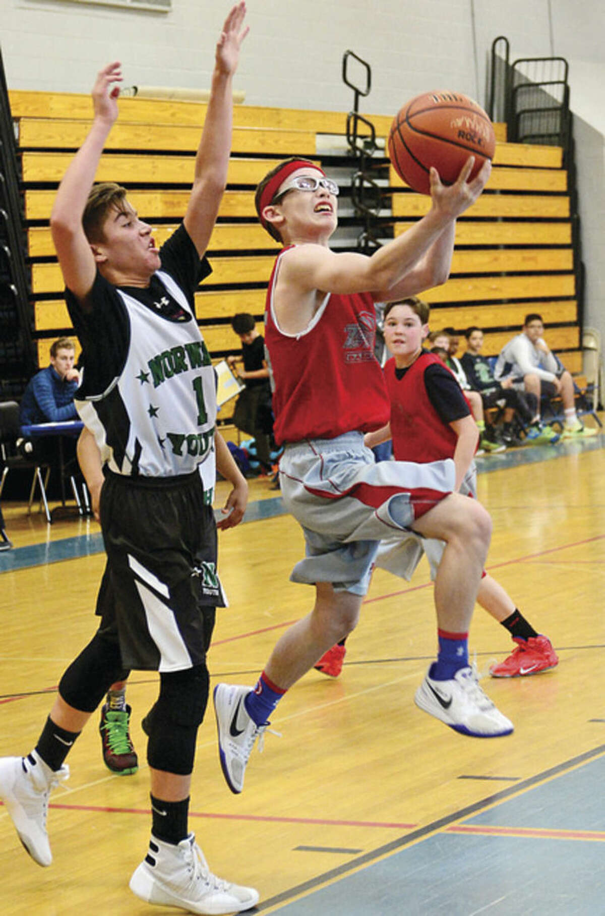 Hour photo / Erik Trautmann Austin Hall of TMT, right, puts up a shot as Peter Meyerson of Norwalk Youth defends during the seventh grade championship game of the Fairfield County Basketball League on Saturday at Ridgefield High. TMT defeated Youth 55-46 to claim the title.