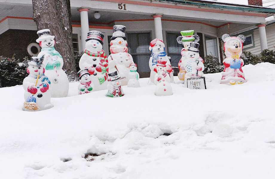 Hour photo / Erik Trautmann A family of snowmen await the snowstorm Saturday evening.