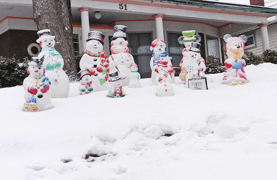 Hour photo / Erik Trautmann A family of snowmen await the snowstorm Saturday evening.