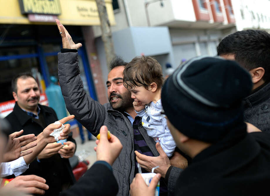 A man reacts as riot police use tear gas and water cannons to disperse people gathered in support outside the headquarters of Zaman newspaper in Istanbul, Saturday, March 5, 2016. Police have erected fences and are standing watch in front of the headquarters of Turkey's largest-circulation newspaper a day after it used tear gas and water cannons to storm the building and enforce a court-ordered seizure. The seizure of Zaman newspaper and its sister outlets Friday has escalated fears over media freedom in Turkey. (AP Photo/Akin Celiktas)