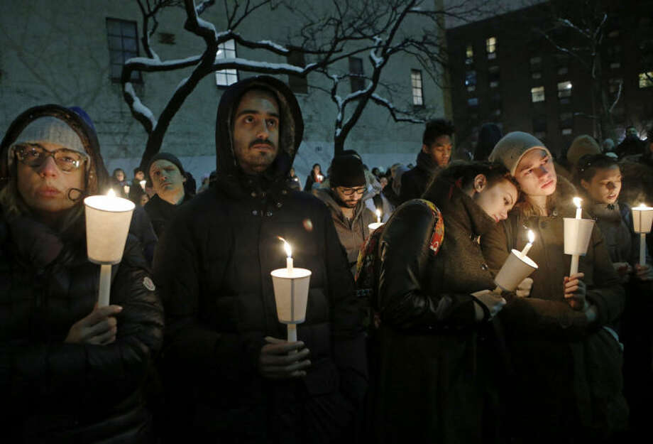 People listen to actor Eric Bogosian speak during a candlelight vigil for actor Philip Seymour Hoffman at the Bank Street Theater, home of the Labyrinth Theater Company, Wednesday, Feb. 5, 2014, in New York. Hoffman died Sunday of a suspected drug overdose. (AP Photo/Kathy Willens)