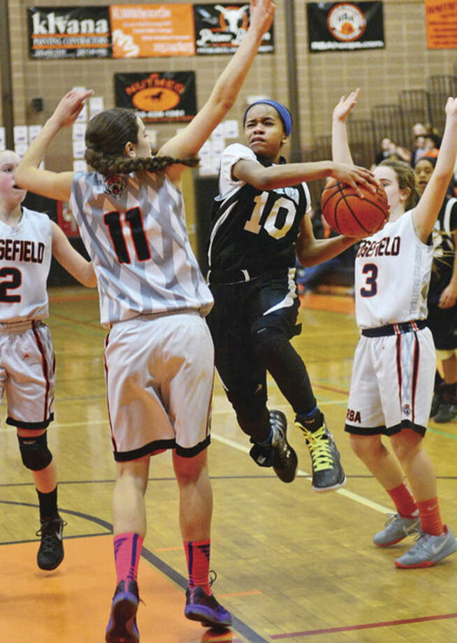 Hour photo / Erik TrautmannNorwalk eighth grade girls youth basketball player Carsyn Langhorn battles Ridgefield to the hoop in the FCBL Championships Saturday in Ridgefield.