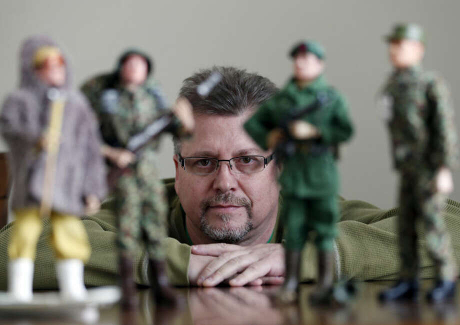 In this Jan. 31, 2014 photo Tearle Ashby poses with some of his G.I. Joe action figures in Niskayuna, N.Y. A half-century after the 12-inch doll was introduced at a New York City toy fair, the iconic action figure is being celebrated by collectors with a display at the New York State Military Museum, while the toy's maker plans other anniversary events to be announced later this month. (AP Photo/Mike Groll)