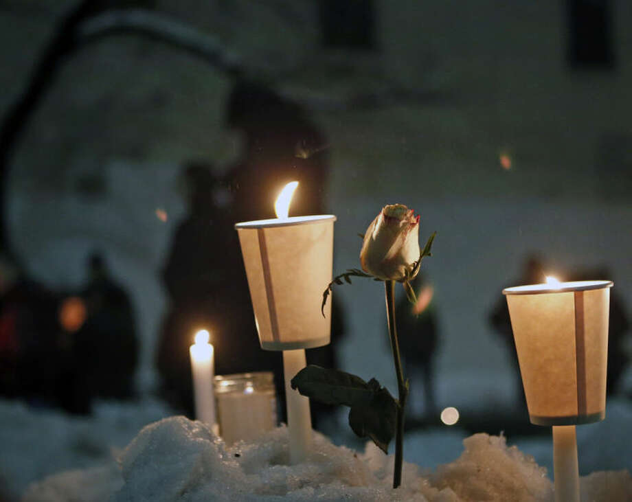 Candles burn alongside a rose left in a snowbank following a candlelight vigil sponsored by the Labyrinth Theater Company in the courtyard of the Bank Street theater for actor Philip Seymour Hoffman, a company member and former Labyrinth artistic director, Wednesday, Feb. 5, 2014, in New York. Hoffman died on Sunday of a suspected drug overdose. (AP Photo/Kathy Willens)