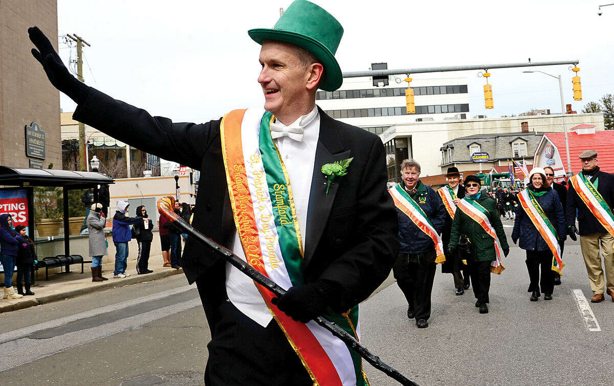 Hour photo / Erik Trautmann The Grand Marshal Andrew McDonald waves to the crowd during the 2016 Stamford St. Patrick's Day Parade Saturday.