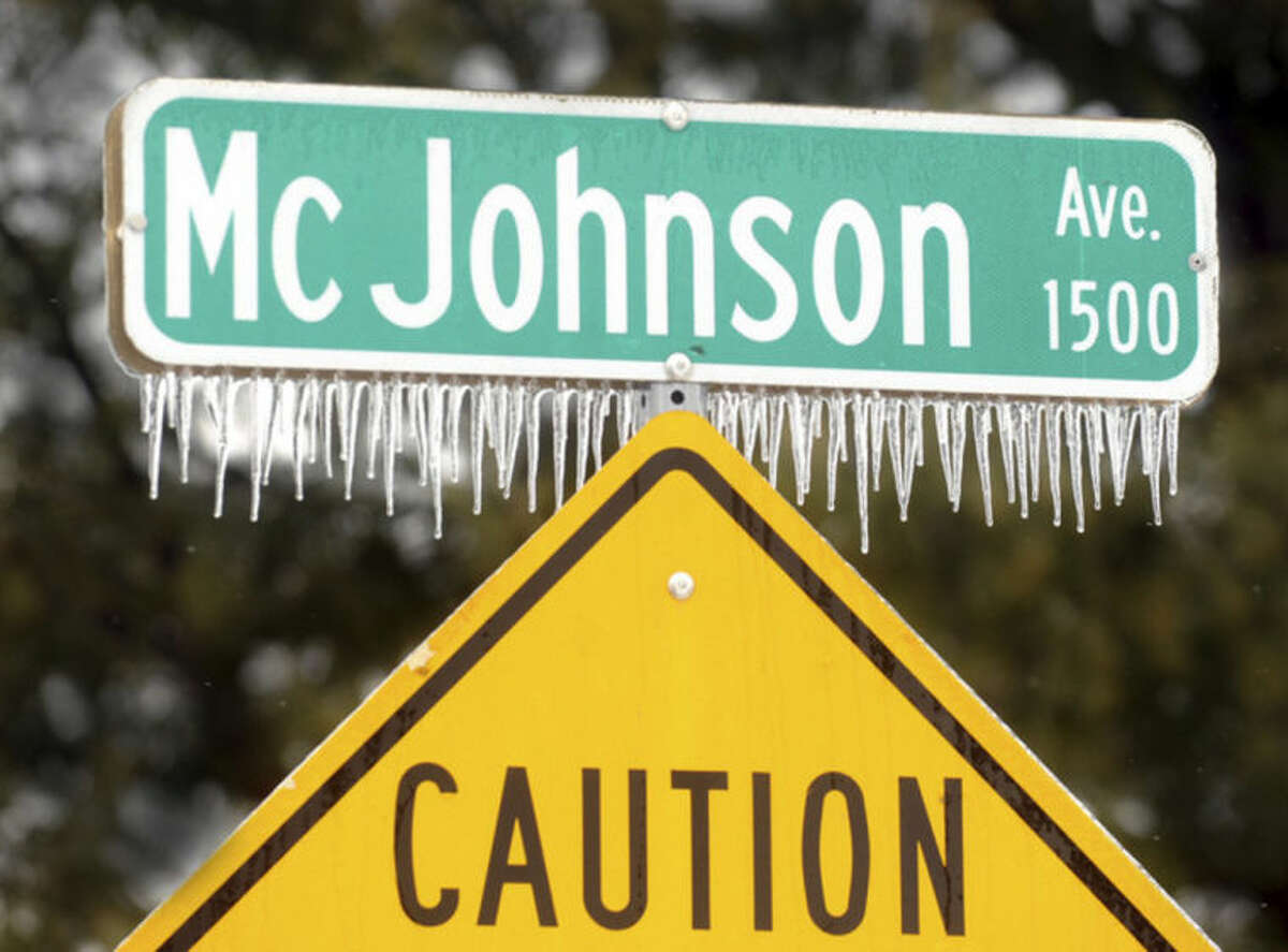 Icicles cling to the McJohnson Avenue street sign ,Wednesday, Feb. 5, 2014, in Owensboro, Ky. (AP Photo/The Messenger-Inquirer, John Dunham)