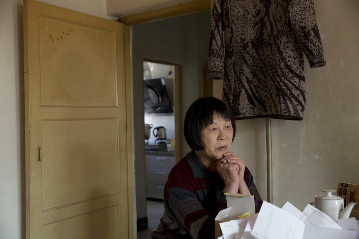 In this photo taken Tuesday, Feb. 23, 2016, Dai Shuqin, who lost her younger sister and the younger sister's extended family when the Malaysia Airlines Flight 370 disappeared nearly two years ago with 239 people on board, pauses during an interview at her home in Beijing. Nearly every day, Dai Shuqin goes to the Malaysia Airlines office, hand-delivering a letter that nearly always says the same thing: