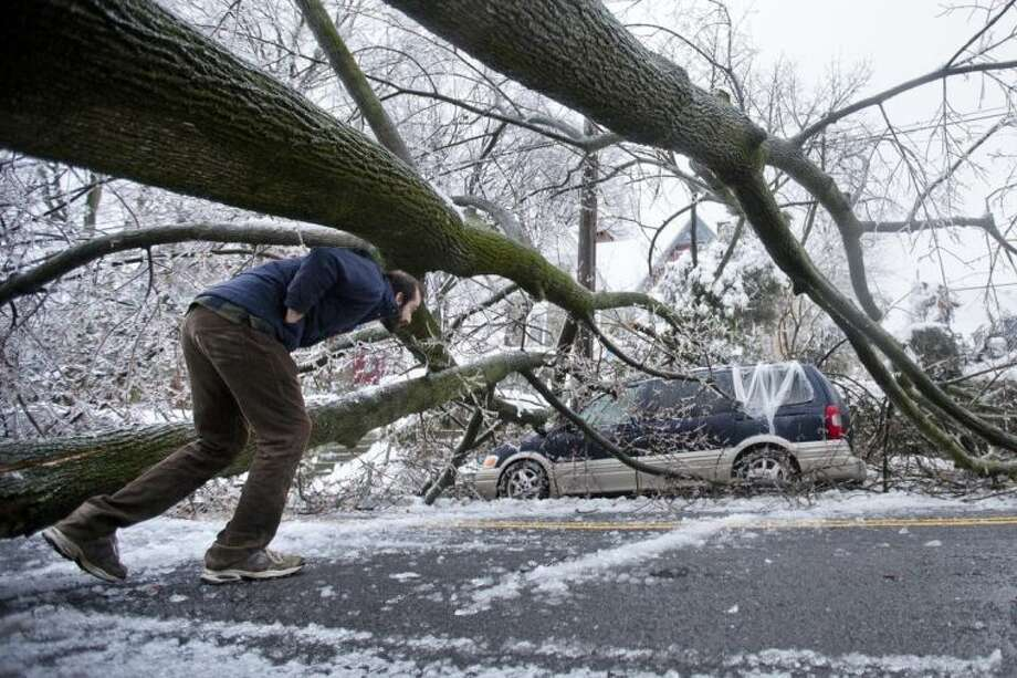 A man inspects an ice covered downed tree that took out an utility line and landed atop a minivan, after a winter storm Wednesday, Feb. 5, 2014, in Philadelphia. Icy conditions have knocked out power to more than 200,000 electric customers in southeastern Pennsylvania and prompted school and legislative delays as well as speed reductions on major roadways. (AP Photo/Matt Rourke)