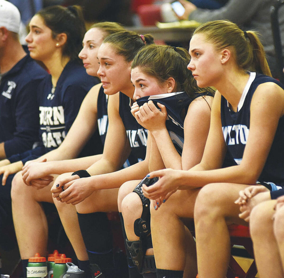 Wilton High senior girls basketball players, from left, Caraline Higgins, Christina Holmgren, Hana Previte, Sarah Fitzgerald and Karen Brosko react as the final seconds tick down on the Warriors' 41-34 Class LL state tournament second round loss at Alumni Gym in Norwich on Thursday.
