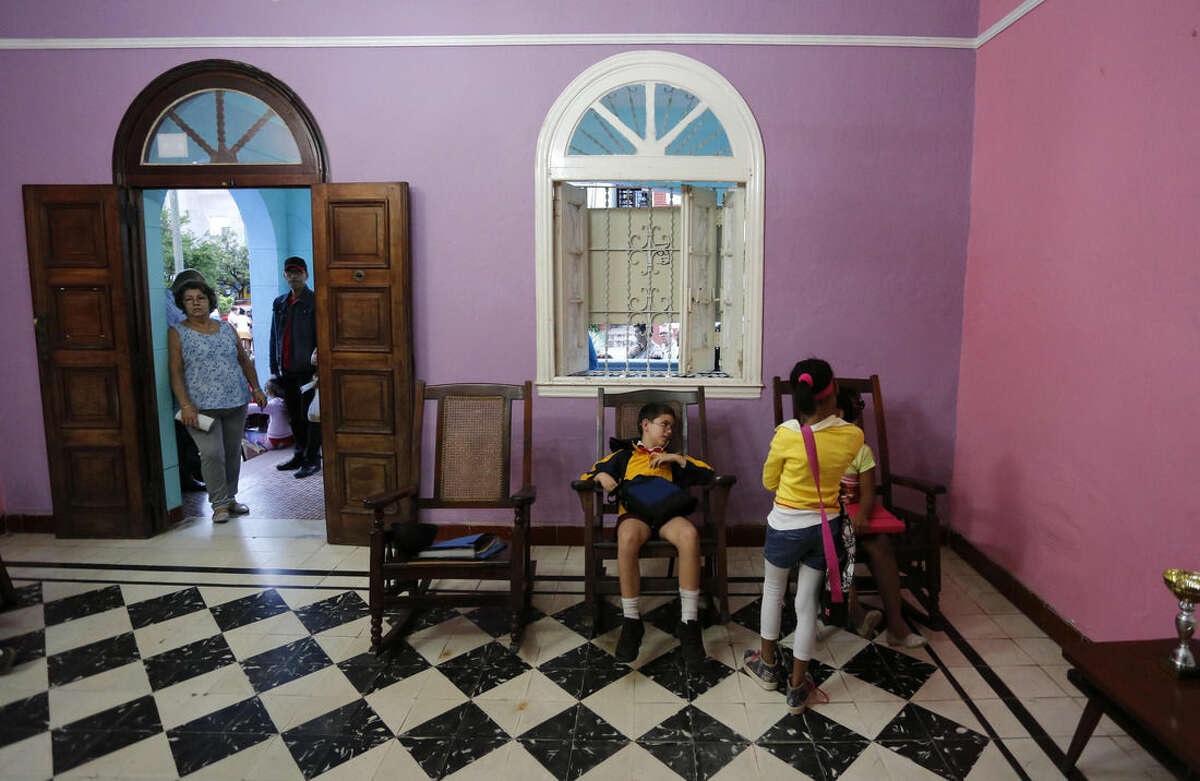 In this Feb. 5, 2016 photo, students sit in rocking chairs in the hallway of the Cuban School of Foreign Languages, before the start of their English class, in Havana, Cuba. Private schools remain illegal except for children of diplomats and foreign business people. Even the Catholic Church cannot open parochial schools. Despite ideological and legal hurdles, Cuba's blooming entrepreneurial system has quietly created something that looks very much like a private education sector over the last half-decade, with thousands of students across Cuba enrolled in dozens of afterschool and weekend foreign language and art schools. (AP Photo/Desmond Boylan)