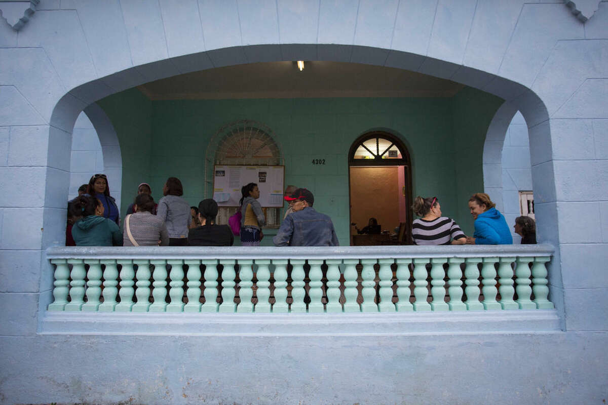 In this Feb. 5, 2016 photo, parents mingle as they wait for their children to be let out of an English lesson at the Cuban School of Foreign Languages, in Havana, Cuba. Despite ideological and legal hurdles, Cuba's blooming entrepreneurial system has quietly created something that looks very much like a private education sector over the last half-decade, with thousands of students across Cuba enrolled in dozens of afterschool and weekend foreign language and art schools. (AP Photo/Desmond Boylan)