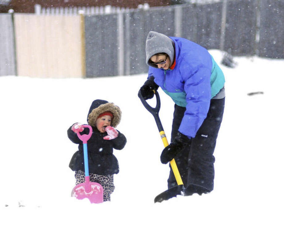 While Lauren Berthiaume, right, shovels her sidewalk, her 17-month-old daughter Rylie Bartusek prefers eating the snow, Wednesday, Feb. 5, 2014, in Worcester, Mass. (AP Photo/Worcester Telegram & Gazette, Steve Lanava)