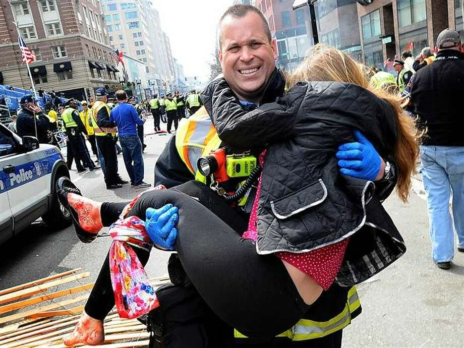 Boston firefighter Jimmy Plourde carries injured Victoria McGrath away from the scene after a bombing near the finish line of the Boston Marathon in Boston. The FBI's investigation into the bombings at the Boston Marathon.