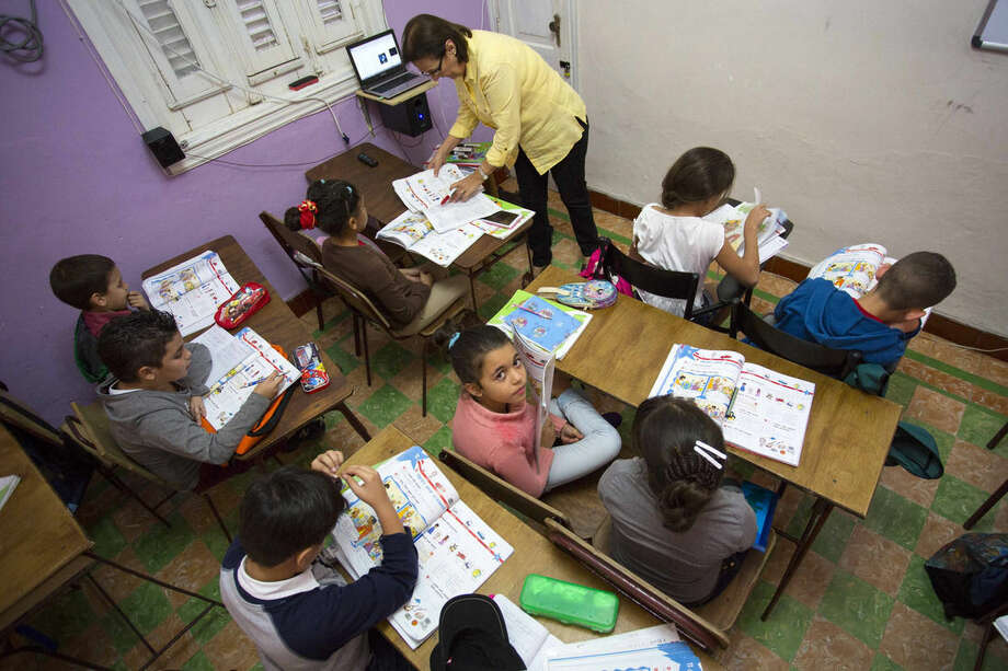 In this Feb. 5, 2016 photo, students attend an English class at the Cuban School of Foreign Languages, in Havana, Cuba. Despite ideological and legal hurdles, Cuba's blooming entrepreneurial system has quietly created something that looks very much like a private education sector over the last half-decade, with thousands of students across Cuba enrolled in dozens of afterschool and weekend foreign language and art schools. (AP Photo/Desmond Boylan)